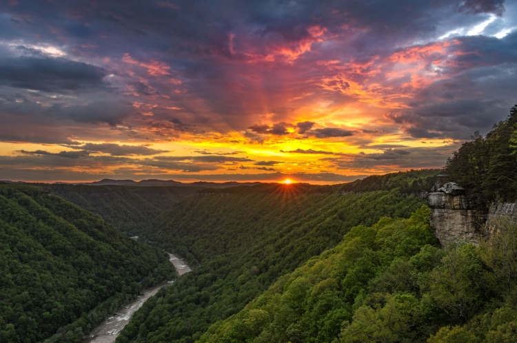 The sun's rays leave behind an explosion of colors as the storm clouds break over the New River Gorge from Beauty Mountain.