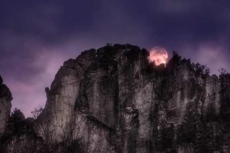 The full moon appears to be cradled by the sheer rock cliff walls of Seneca Rocks as it rises amidts the gathering night time clouds. Pendleton County, West Virginia, USA.