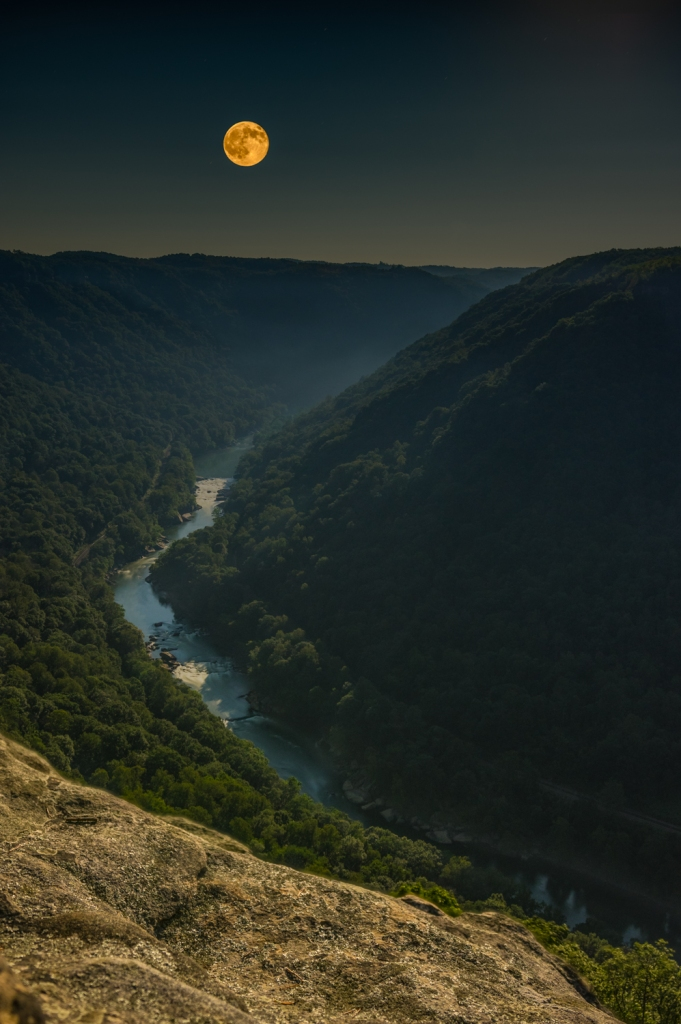 The full, new moon rising over the New River Gorge as viewed from the Diamond Point overlook of the Endless Wall Trail, West Virginia.